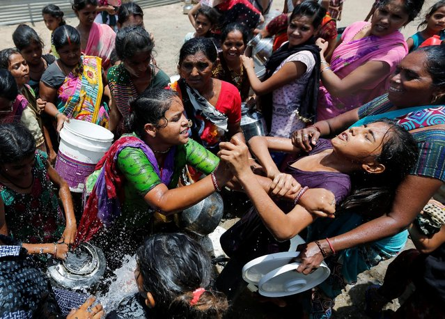 Local residents fight to collect free drinking water from municipal corporation tanker on a hot summer day on the outskirts of Ahmedabad, India June 1, 2016. (Photo by Amit Dave/Reuters)
