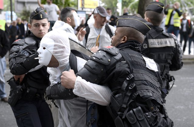French riot police detain an employees of Seita, a subsidiary of Imperial Tobacco, wearing a white suit and mask with a cigarette in his mouth, during a demonstration outside the company's headquarters in Paris on June 17, 2014. More than 200 employees protested against the restructuring plan of the company, details of which were announced to unions at an Extraordinary Central Works Council. (Photo by Stephane De Sakutin/AFP Photo)