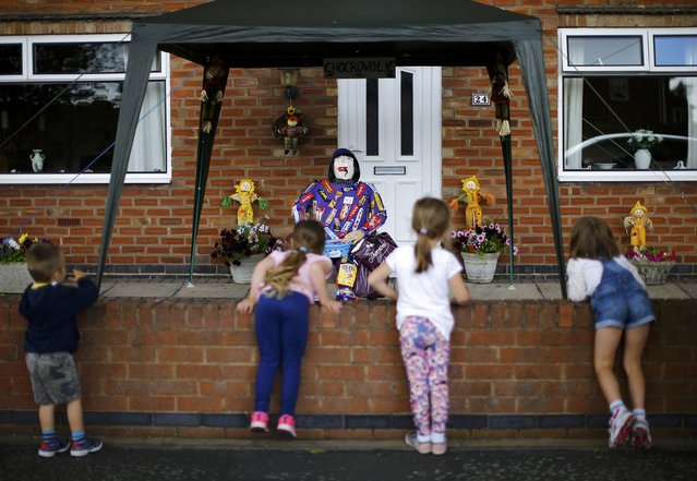 "Children look at a scarecrow titled ""Chocrowolic"" during the Scarecrow Festival in Heather, Britain July 29, 2015. (Photo by Darren Staples/Reuters)"