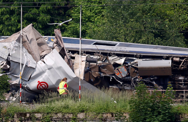 An official inspects the wreckage of a passenger train after it crashed into the back of a freight train, in the eastern Belgian municipality of Saint-Georges-Sur-Meuse, June 6, 2016. (Photo by Francois Lenoir/Reuters)
