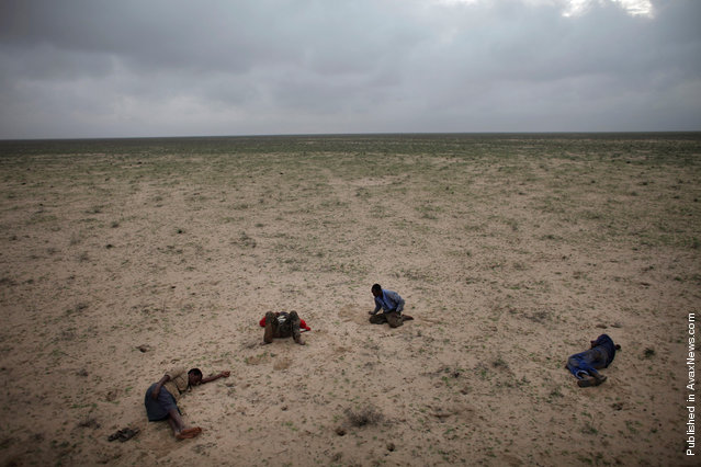 In this photo released by Word Press Photo, the 1st Prize Contemporary Issues Stories by Ed Ou, Canada, Reportage by Getty Images, shows four Somali refugees en route to Yemen sleep in the desert after traveling all night on muddy roads and in pouring rain, Somaliland, March 15, 2010