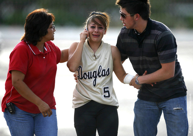 Douglas High School softball player Stephanie Ybarra is consoled after her father and Douglas assistant coach David Ybarra was taken to the hospital by ambulance after suffering a heart attack in the dugout before the game