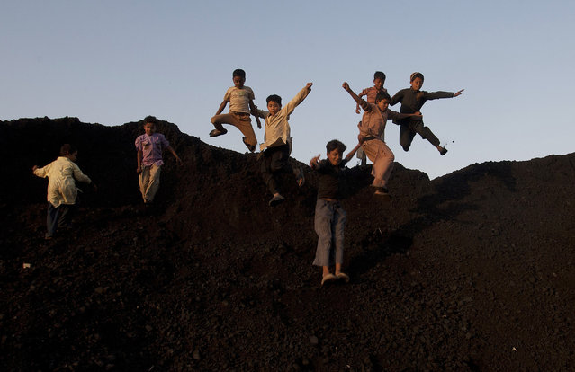 Pakistani children jump down as they play on stock pile of coal in Karachi, Pakistan, Tuesday, March 15, 2016. (Photo by Shakil Adil/AP Photo)