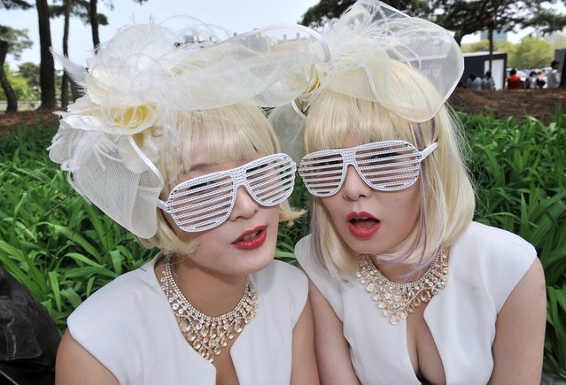 South Korean women dressed in costumes pose as they wait for a concert by US pop diva Lady Gaga outside Seoul's Olympic Stadium. Some religious groups in South Korea have opposed the concert, saying Lady Gaga has advocated homosexuality and performed in an explicitly sexual manner