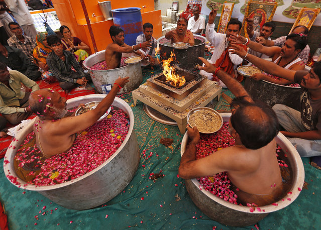 """Hindu priests sit in cauldrons of water and make offerings to in front of a fire while performing the """"Parjanya Varun Yagam"""", a special prayer for rain, in the western Indian city of Ahmedabad July 1, 2014. India's monsoon rainfall was 43 percent below average in June, the weather office said on Monday, the weakest first month of the season in five years. (Photo by Amit Dave/Reuters)"""