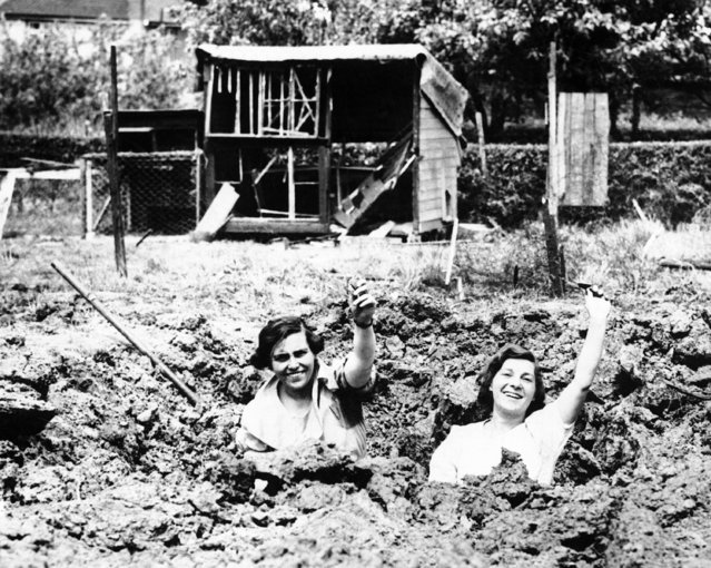 Two girls stand in the crater caused by the explosion of a bomb dropped from a German plane at a small town in Essex, England, May 25, 1940. This bomb dropped in a yard, wrecking the hen coop in background. A girl was injured elsewhere in Essex and 11 men were injured in Yorkshire by bombs the same day. (Photo by AP Photo)