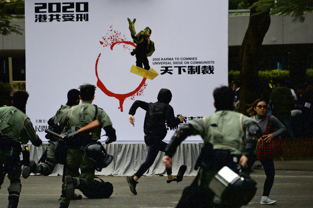 Riot police chase a masked man ahead of a rally demanding electoral democracy and call for boycott of the Chinese Communist Party and all businesses seen to support it in Hong Kong, Sunday, January 19, 2020. (Photo by Ng Han Guan/AP Photo)