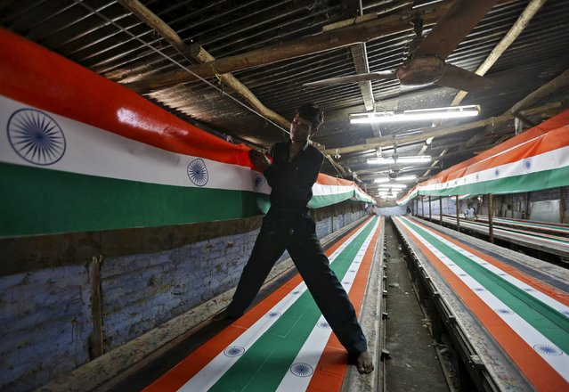 A worker hangs Indian national flags for drying inside a textile printing workshop ahead of the Independence Day celebrations in Ahmedabad, India, August 10, 2015. India commemorates its Independence Day on August 15. (Photo by Amit Dave/Reuters)