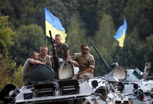 Ukrainian servicemen sit onboard an armored personnel carrier after a military drill at a shooting range near Zhytomyr, Ukraine, August 11, 2015. (Photo by Valentyn Ogirenko/Reuters)