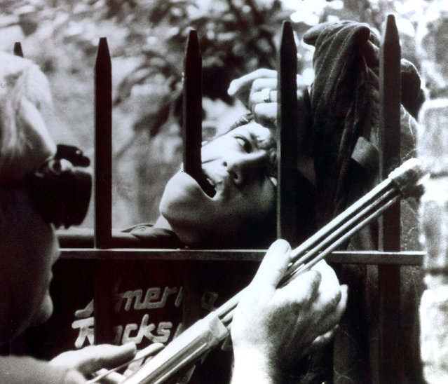 Fifteen-year-old Julio Castillo eyes firefighters and emergency services police as they work with cutting torches to remove the section of fence which pierced his jaw at 47-15 48th St. in the Queens borough of New York, July 8, 1989.  Castillo was impaled when he slipped while trying to scale the fence, and he was transported to the hospital with the metal bars still in place.  Castillo recovered with no significant injury. (Photo by Steve Spak/AP Photo)