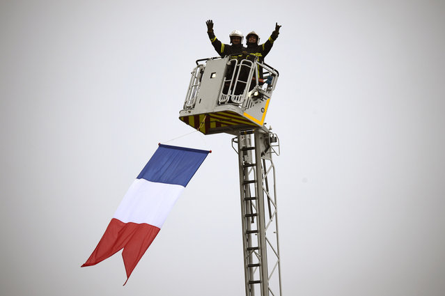 Firefighters wave from a cherry picker during the 161 km eighth stage of the 101st edition of the Tour de France cycling race on July 12, 2014 between Tomblaine and Gerardmer La Mauselaine, eastern France. (Photo by Lionel Bonaventure/AFP Photo)
