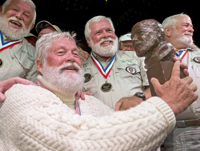 "Wally Collins holds a bust of author Ernest Hemingway after winning the 2014 ""Papa"" Hemingway Look-Alike Contest in this handout photo provided by the Florida Keys News Bureau at Sloppy Joe's Bar in Key West, Florida July 19, 2014. Collins, a Phoenix resident, won the title on his sixth try during the event that was the highlight of Key West's annual Hemingway Days festival. (Photo by Andy Newman/Reuters/Florida Keys News Bureau)"