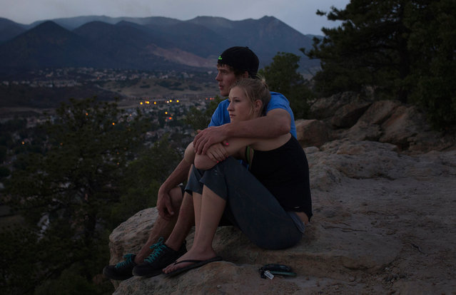 Residents Lindsay Hetzel and Nathan Birdseye sit on a cliff overlooking the Waldo Canyon fire in Colorado Springs, on June 30, 2012. Crews battling a deadly Colorado wildfire ranked the most destructive in state history have made enough headway to allow most evacuees home, but concerns remain about rogue bears and burglaries in vacant houses, officials said. (Reuters/Adrees Latif)