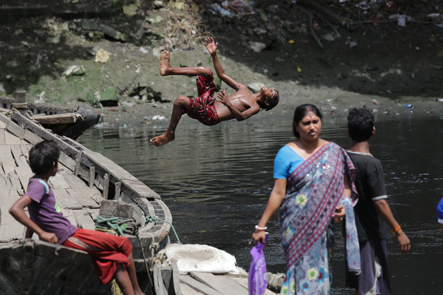 An Indian boy dives into the river to collect coins from the polluted river Adi Ganga next to Kalighat temple in Calcutta, eastern India, 28 June 2016. At least a hundred boys earn their income by collecting coind which were thrown in to the river as an offering by devotees to the the holy river.They collect coins worth between one US dollar and 10 US dollars per day, which often is their and or their family's only source of income. (Photo by Piyal Adhikary/EPA)