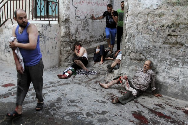 Wounded Palestinians wait for medics to arrive shortly after an Israeli airstrike on a market place in the Shejaiya neighbourhood near Gaza City, 30 July 2014. On the 23rd day of the Israeli offensive in Gaza the death toll there has reached 1,283. More than 7,150 people have been wounded. (Photo by Sameh Rahmi/EPA)