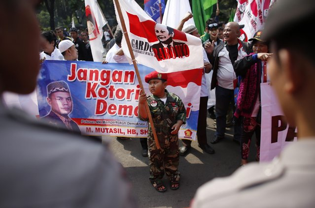 """A boy takes part in a protest by supporters of losing presidential candidate Prabowo Subianto, who is contesting last month's presidential election result, outside the Constitutional Court in Jakarta August 8, 2014. Prabowo launched a last-gasp attempt to overturn the official election result on Wednesday, telling the nation's highest court last month's vote was tainted by """"massive"""" fraud. (Photo by Darren Whiteside/Reuters)"""
