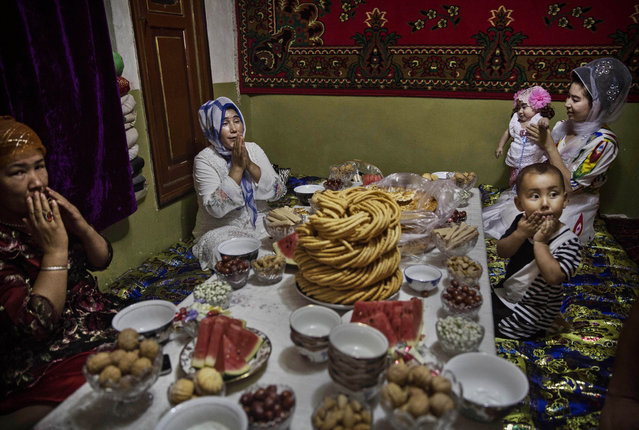 A Uyghur family pray before lunch on the Eid holiday on July 29, 2014 in old Kashgar, Xinjiang Province, China. (Photo by Kevin Frayer/Getty Images)