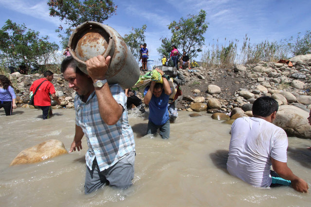 People carry their belongings across the Tachira River from San Antonio del Tachira, Venezuela, toward Colombia, Tuesday, August 25, 2015. (Photo by Eliecer Mantilla/AP Photo)