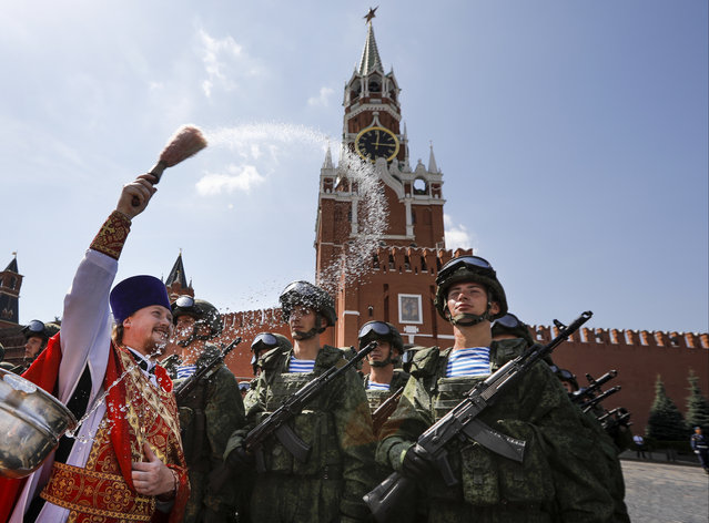In this file photo taken on Wednesday, Aug. 2, 2017 Russian Orthodox priest blesses paratroopers during celebrations of Paratroopers Day in the Red Square in Moscow, Russia. The Russian military says major war games, the Zapad (West) 2017 maneuvers, set for next month will not threaten anyone. (Photo by Alexander Zemlianichenko/AP Photo)