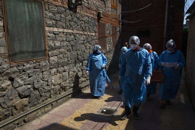 Kashmiri health workers walk inside a residential area during a contact-tracing drive after the first person in the region was tested positive for COVID-19 in Srinagar, Indian controlled Kashmir, Thursday, March 19, 2020. (Photo by Dar Yasin/AP Photo)