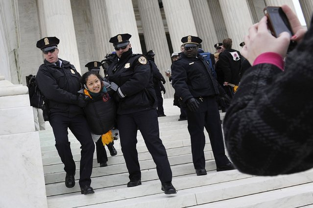 Police arrest demonstrators after they tore down a barricade and took to the steps of the U.S. Supreme Court building in Washington, in this file photo taken January 20, 2012. A U.S. appeals court on Friday upheld a federal law banning protests on the marble plaza directly in front of the U.S. Supreme Court in Washington, saying demonstrators are free to protest nearby. (Photo by Jonathan Ernst/Reuters)