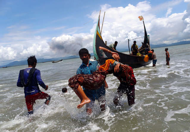 Smoke is seen on Myanmar's side of border as an exhausted Rohingya refugee woman is carried to the shore after crossing the Bangladesh-Myanmar border by boat through the Bay of Bengal, in Shah Porir Dwip, Bangladesh September 11, 2017. (Photo by Danish Siddiqui/Reuters)