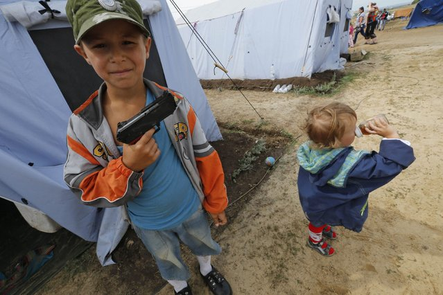Maxim, 7, who arrived from the eastern Ukrainian town of Horlivla (Gorlovka), poses with a toy gun at a temporary tent camp set up for Ukrainian refugees outside Donetsk, located in Russia's Rostov region near the Russian-Ukrainian border, August 18, 2014. (Photo by Alexander Demianchuk/Reuters)