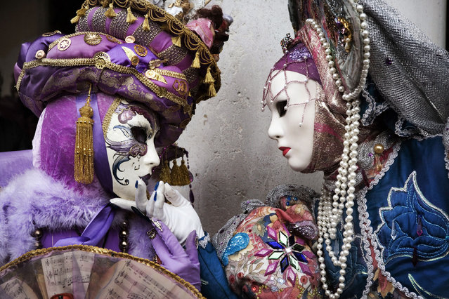 Masked participants stand in St.Mark's Square during the Carnival on February 10, 2007 in Venice, Italy.  (Photo by Marco Di Lauro)