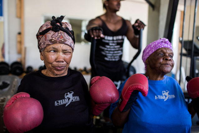 "77 year-old Gladys Ngwenya (L) winces as she chews on a piece of ginger before a ""Boxing Gogos"" (Grannies) session hosted by the A Team Gym in Cosmo City in Johannesburg on September 19, 2017. (Photo by Gulshan Khan/AFP Photo)"