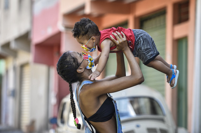 Carolaine Reis and her son Miguel Alves, residents of the Aglomerado da Serra favela, wear a protective mask against the spread of the new Coronavirus (COVID-19) made by the seamstresses of the Remexe Favelinha studio, in the Aglomerado da Serra favela, on April 13, 2020 in Belo Horizonte, Brazil. Facial masks follow the protocol and guidelines defined by the Ministry of Health. Around 6,000 masks have already been produced. The masks are being distributed to a part of the population and sold throughout the country, in the amount of 5 reais per unit. (Photo by Pedro Vilela/Getty Images)