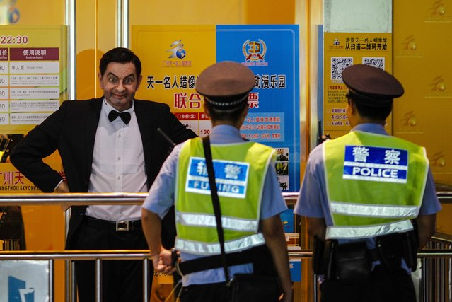 Policemen look at a wax figure of Rowan Atkinson, dressed as his popular television character Mr. Bean, on display outside a wax figure museum in Guangzhou, Guangdong province, August 24, 2014. (Photo by Alex Lee/Reuters)