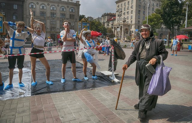 Young people perform a routine to attract public attention to the problem of human trafficking, as an elderly woman passes by, during a protest in central Kiev, Ukraine, Friday, July 29, 2016. The United Nations General Assembly has declared July 30 as World Day against Trafficking in Persons. (Photo by Efrem Lukatsky/AP Photo)