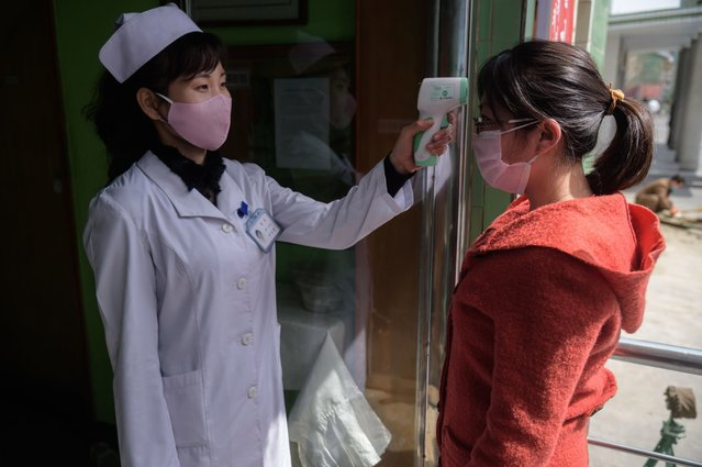 A health worker takes the temperature of a woman amid concerns over the COVID-19 coronavirus, at an entrance of the Pyongchon District People's Hospital in Pyongyang on April 1, 2020. (Photo by Kim Won Jin/AFP Photo)