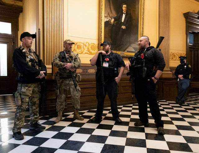 Members of a militia group stand near the doors to the chamber in the capitol building before the vote on the extension of Governor Gretchen Whitmer's emergency declaration/stay-at-home order due to the coronavirus disease (COVID-19) outbreak, in Lansing, Michigan, U.S. April 30, 2020. (Photo by Seth Herald/Reuters)