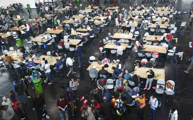 Migrants eat at a makeshift mensa at the fair ground of Munich, Germany September 7, 2015. (Photo by Michaela Rehle/Reuters)