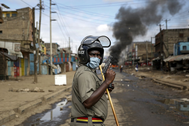 A police officer holds a pistol during clashes with protesters near a burning tyre barricade in the Kariobangi slum of Nairobi, Kenya Friday, May 8, 2020. Hundreds of protesters blocked one of the capital's major highways with burning tires to protest government demolitions of the homes of more than 7,000 people and the closure of a major food market, causing many to sleep out in the rain and cold because of restrictions on movement due to the coronavirus. (Photo by Brian Inganga/AP Photo)