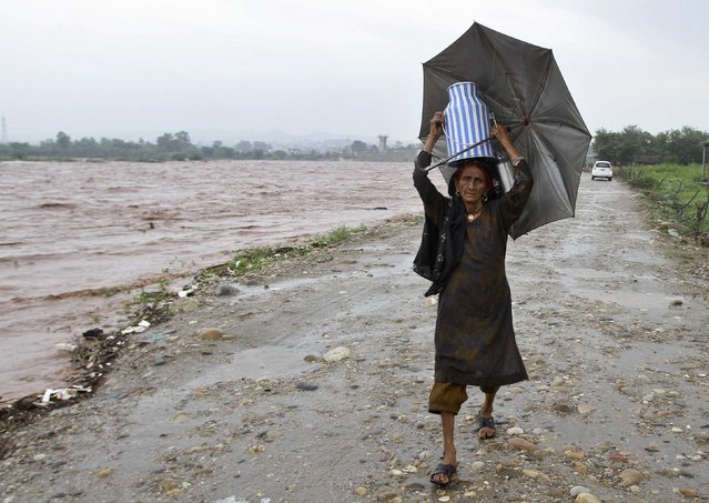A nomadic woman carries a milk container while shifting her belongings to a safer place from the flooded banks of river Tawi after heavy rains in Jammu September 5, 2014. Sixty-five people were killed after heavy rains caused flash floods in Indian-administered Kashmir, including a wedding party on a bus that was swept away, officials said on Thursday. (Photo by Mukesh Gupta/Reuters)