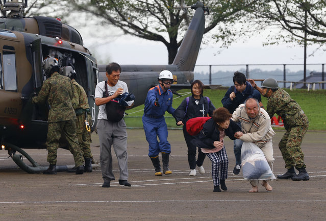 People rescued by a helicopter are brought to an evacuation center in Joso, Ibaraki prefecture, northeast of Tokyo, Friday, September 11, 2015. Search and rescue of residents stranded and missing resumed Friday, a day after raging floodwaters broke through an embankment and swamped the city, washing away houses and forcing dozens of people to rooftops. (Photo by Shizuo Kambayashi/AP Photo)
