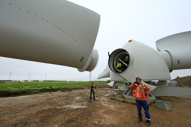 Employees work on the rotor hub of a turbine in Meneslies, France July 22, 2014. (Photo by Benoit Tessier/Reuters)