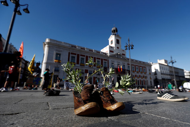 """Branches are put inside a pair of shoes during an action held as part of Extinction Rebellion campaign in Puerta del Sol square, in downtown Madrid, Spain, 29 May 2020. Several similar performances are planned to be held in some cities under the motto """"COVID today, Climate Crisis tomorrow"""". (Photo by Sebastián Mariscal/EPA/EFE)"""