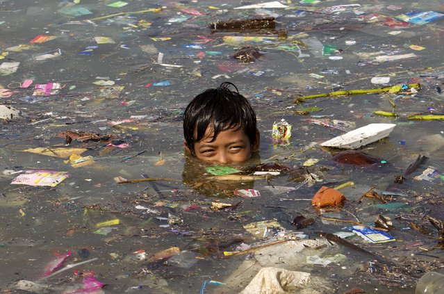 A Filipino boy swims among washed up rubbish in Manila bay, the Philippines, 23 September 2014. Countries and organizations began to announce measures to reduce greenhouse gas emissions and divest in fossil fuels on the one-day UN Climate Summit, where more pledges to reduce climate change are expected. Addressing the controversial issue of taxing or trading in carbon emissions, the World Bank on 22 September 2014, identified at least 73 countries that advocate putting a price on the release of carbon dioxide into the atmosphere. (Photo by Ritchie B. Tongo/EPA)
