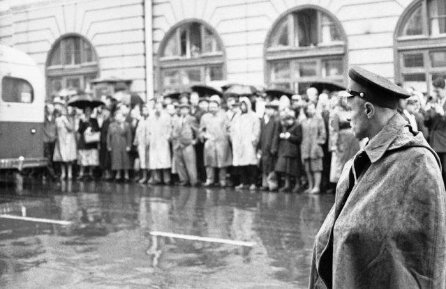 A Moscow policeman, right, watches the crowd gather outside the Great Hall of Columns in Moscow, August 17, 1960, for the opening of the trial for espionage of Francis Gary Powers, pilot of the U-2. Despite the rain the crowd steadily increased. (Photo by AP Photo)