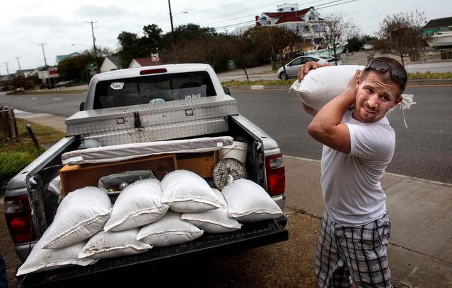 Nick Almeter prepares for the arrival of Hurricane Sandy as he carries sandbags to place by properties along Ocean View Avenue in Norfolk, Virginia on Saturday. (Photo by Ross Taylor/The Virginian-Pilot)