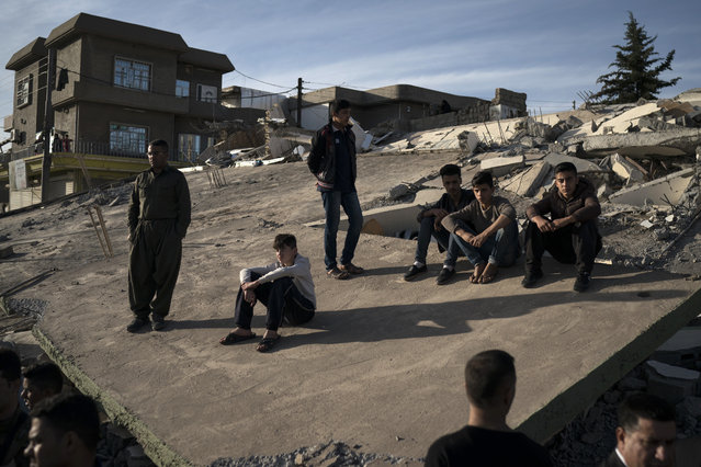 People sit on the roof of a destroyed house after an earthquake, in the city of Darbandikhan, northern Iraq, Monday, November 13, 2017. (Photo by Felipe Dana/AP Photo)