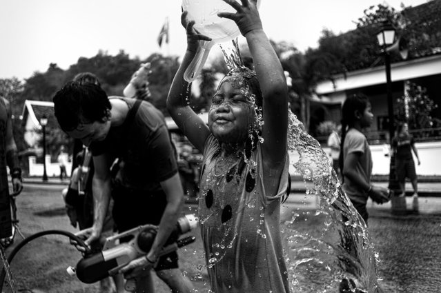 """""""Boun Pi Mai (Water Festival)"""". Every Year in April, during the """"Boun Pi Mai"""" Lao's New Year a huge water fight is taking place in some South Asia country. The whole city of Luang Prabang (Laos) is under water guns. This cute kid was water fighting herself as the festival taking place during the hottest days of the year. Photo location: Luang Prabang, Laos. (Photo and caption by William Kerdoncuff/National Geographic Photo Contest)"""