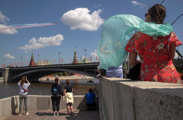 People watch as Russian aircrafts fly above the Kremlin during a military parade, marking the 75th anniversary of the Nazi defeat, in Moscow, Russia, 24 June 2020. The Victory Day military parade normally is held on 09 May, the nation's most important secular holiday, but this year it was postponed due to the coronavirus pandemic. (Photo by Sergei Ilnitsky/EPA/EFE)