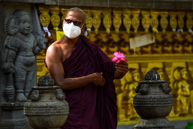 A Buddhist monk prays at the Kelaniya temple during the Poson Poya (full moon) religious festival marking the arrival of Buddhism in the island, on the outskirts of Colombo on June 5, 2020. Sri Lanka on June 5 marked a key Buddhist festival with a nation-wide 24-hour curfew as devotees were urged to remain indoors to help prevent the spread of the coronavirus. (Photo by Ishara S. Kodikara/AFP Photo)