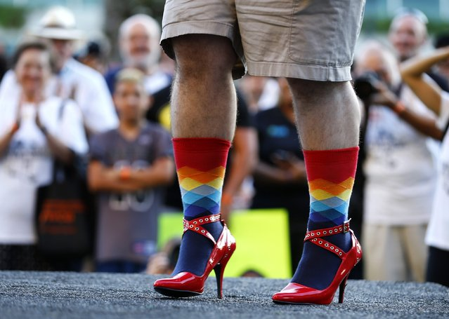 """A man takes part in a fashion show before participating with hundreds of other men and women walking through downtown wearing high heel shoes as part of an event called """"Walk a Mile in Her Shoes"""" to help raise awareness of domestic violence in San Diego, California October 9, 2014. (Photo by Mike Blake/Reuters)"""