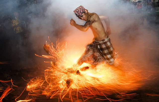 "A Balinese man kicks up fire during the ""Perang Api"" ritual ahead of Nyepi day, which falls on Tuesday in Gianyar on the Indonesian island of Bali March 11, 2013. Nyepi is a day of silence for self-reflection to celebrate the Balinese Hindu new year, where Hindus in Bali observe meditation and fasting, but are not allowed to work, cook, light lamps or conduct any other activities. (Photo by Reuters/Stringer)"