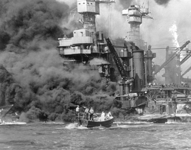 A small boat rescues sailors from the USS 'West Virginia' after she had suffered a hit in the Japanese attack on Pearl Harbor. The USS Tennessee (BB-43) is inboard of the sunken battleship. (Photo by Fox Photos/Getty Images)